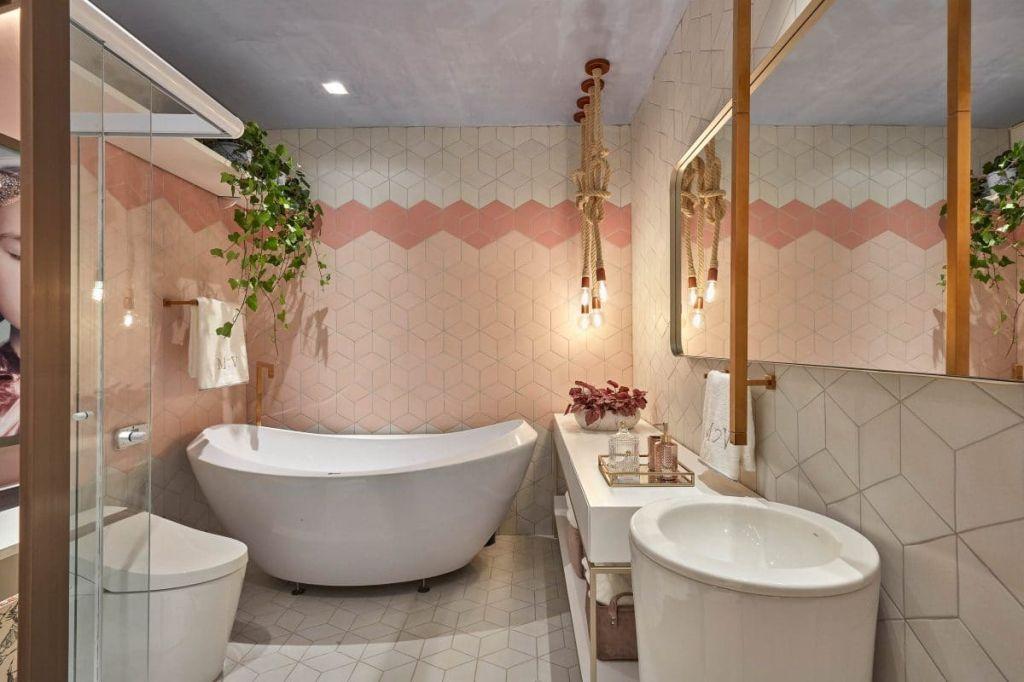 banheiro com paredes cor de rosa e uma planta suspensa na parte de cima da banheira branca