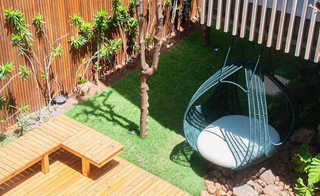 área externa da pousada maria flor com deck de madeira, grama verde e um puf azul turquesa para acomodar os visitantes