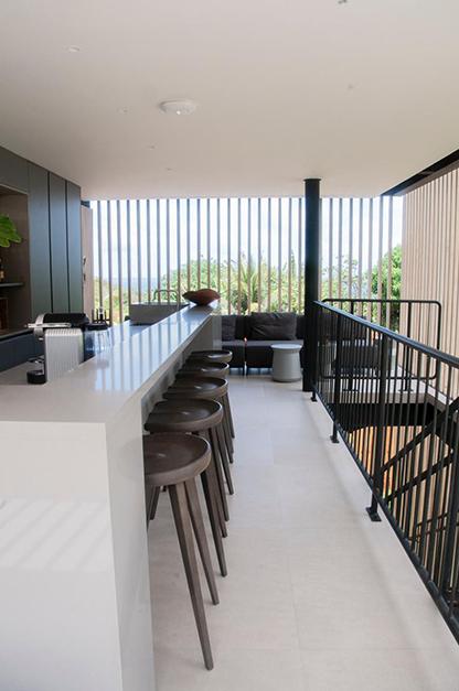 bar com bancada branca e cadeiras em tom chumbo com móvel planejado que acomoda as bebidas em uma tonalidade mais escura