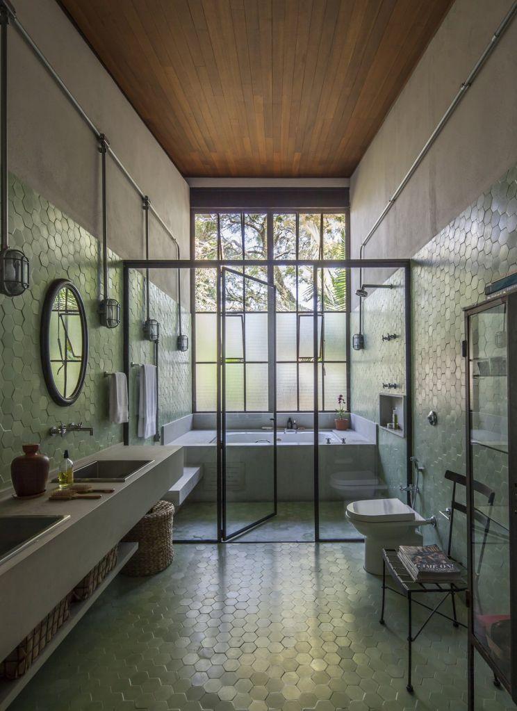 banheiro com revestimento verde na parede espelho e box transparente que abriga uma banheira
