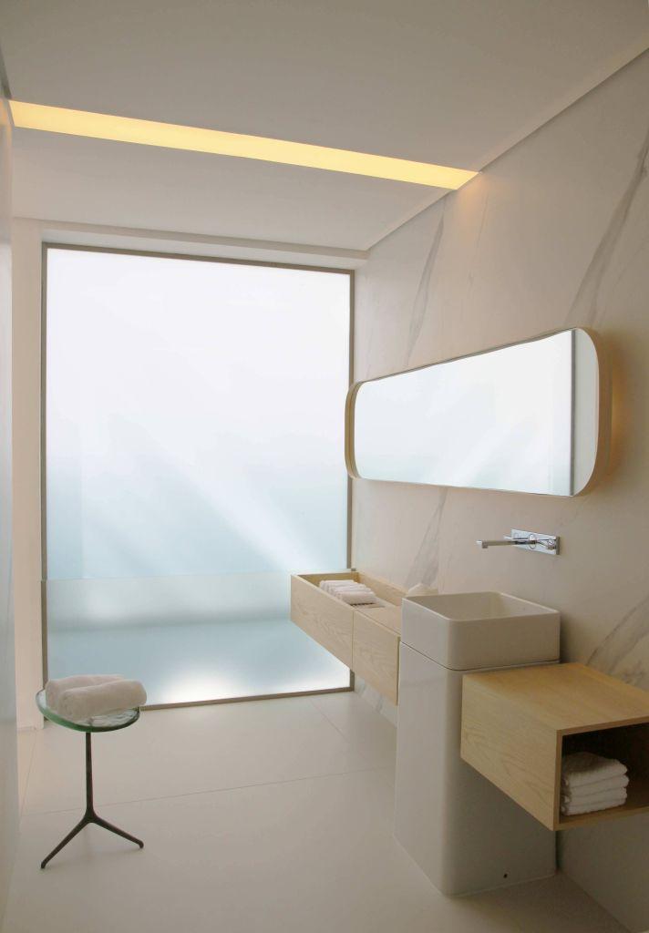 banheiro minimalista com ampla janela para o exterior, uma cuba com a torneira logo acima e um espelho amplo
