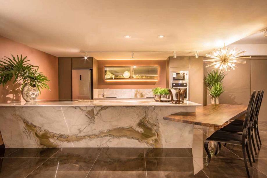 cozinha com ilha de mármore no centro com mesa de madeira lateral integrada
