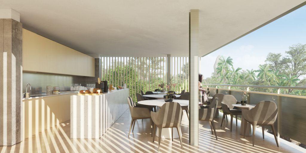 cozinha com bancada branca, painéis de madeira clara. Do lado de fora, cadeiras cinzas e mesas brancas acomodam os visitantes.