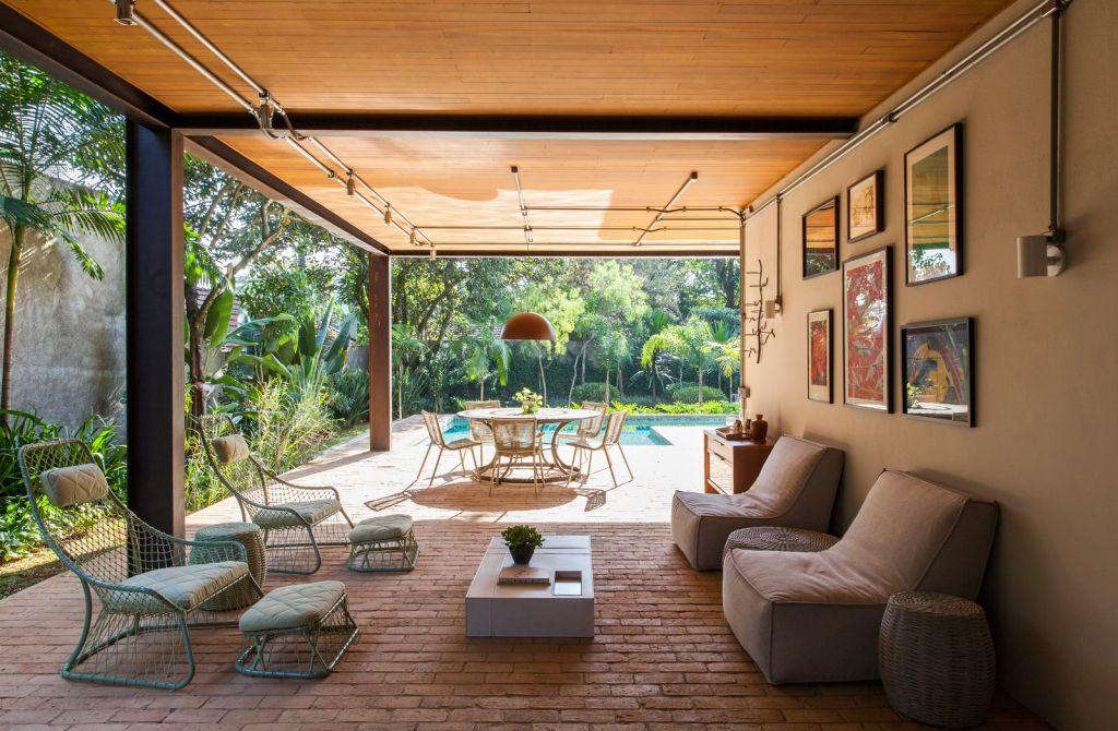 área externa com sofás e quadros na parede e luz natural iluminando o local