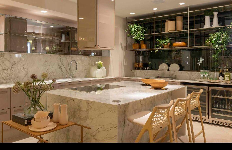 Espaço Deca de uma cozinha com ilha de mármore com duas cadeiras a frente para receber convidados