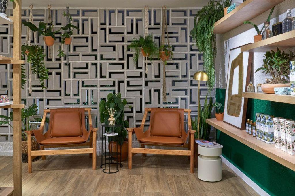 duas poltronas marrom em frente a uma parede texturizada com linhas brancas e pretas se encontrando como em um labirinto. À direita, uma parede verde escuro apoia uma prateleira em madeira clara e um quadro decorativo.