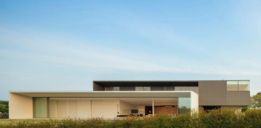 casa branca com piso superior preto e natureza abundante