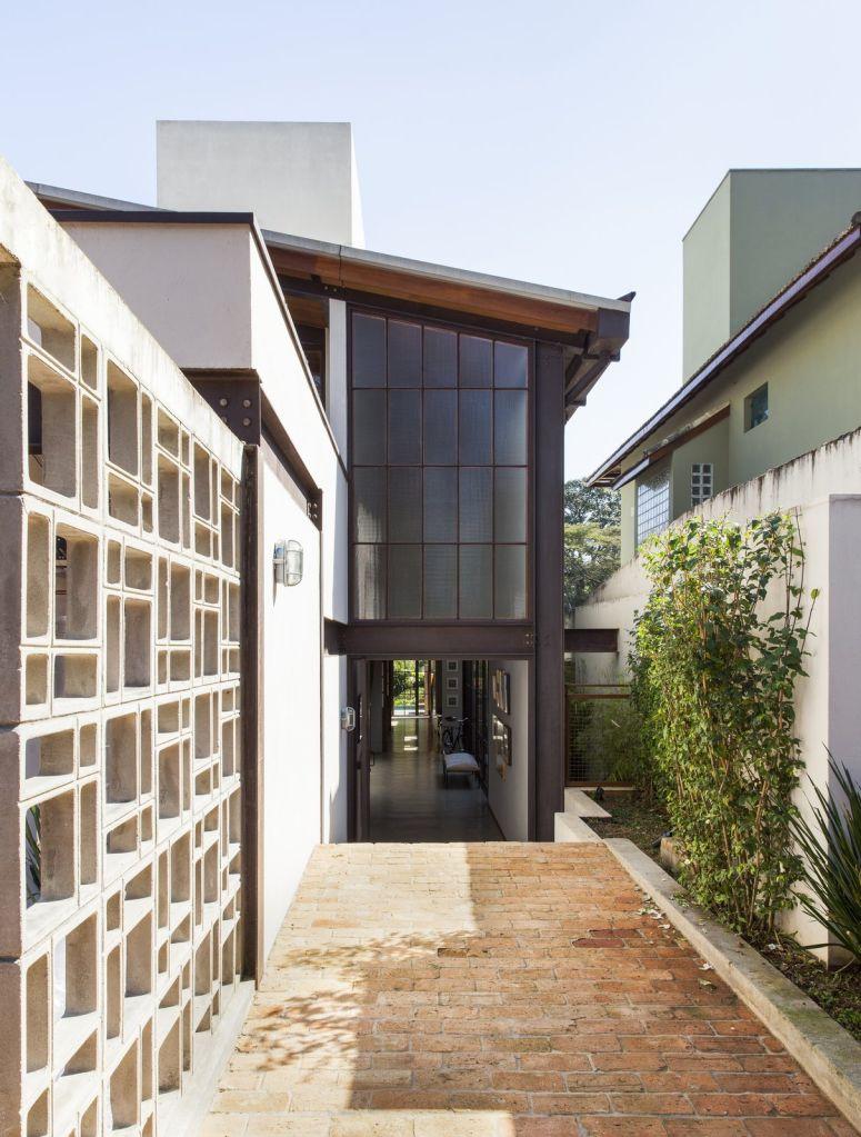 fachada da casa com revestimento em vidro e teto inclinado