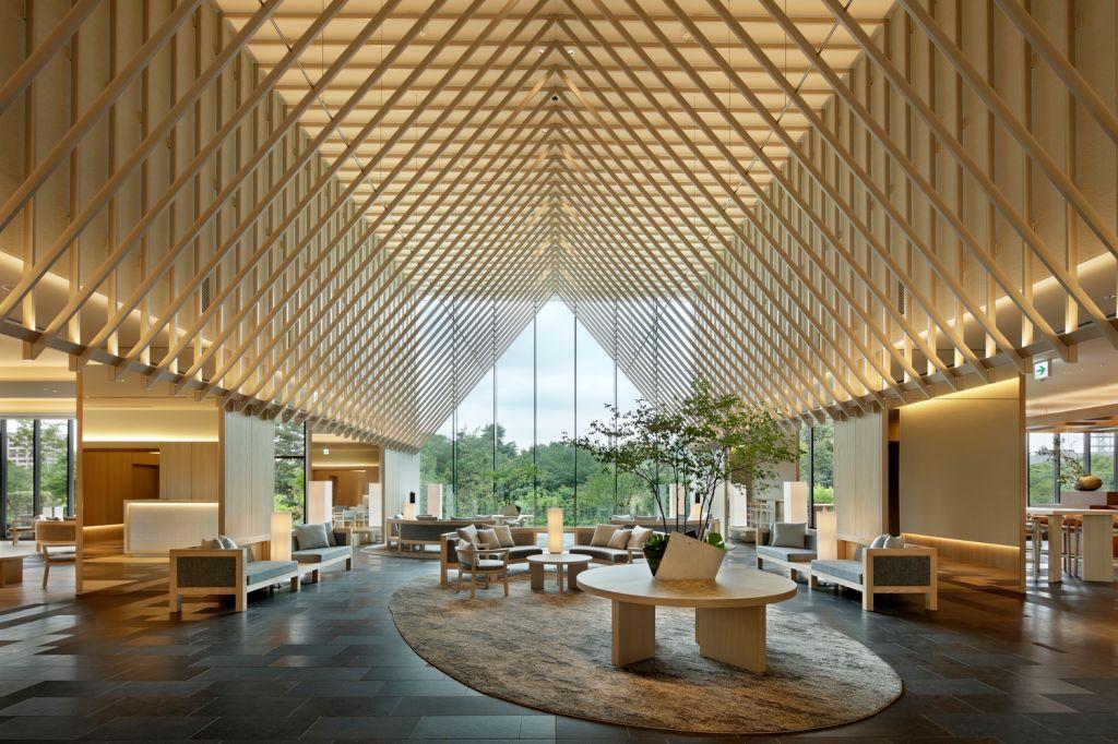 Hall do hotel. Ripas de madeira no teto em formato de cabana. Parede de vidro ao fundo. Tapete oval no centro. Sofás e poltronas espalhados