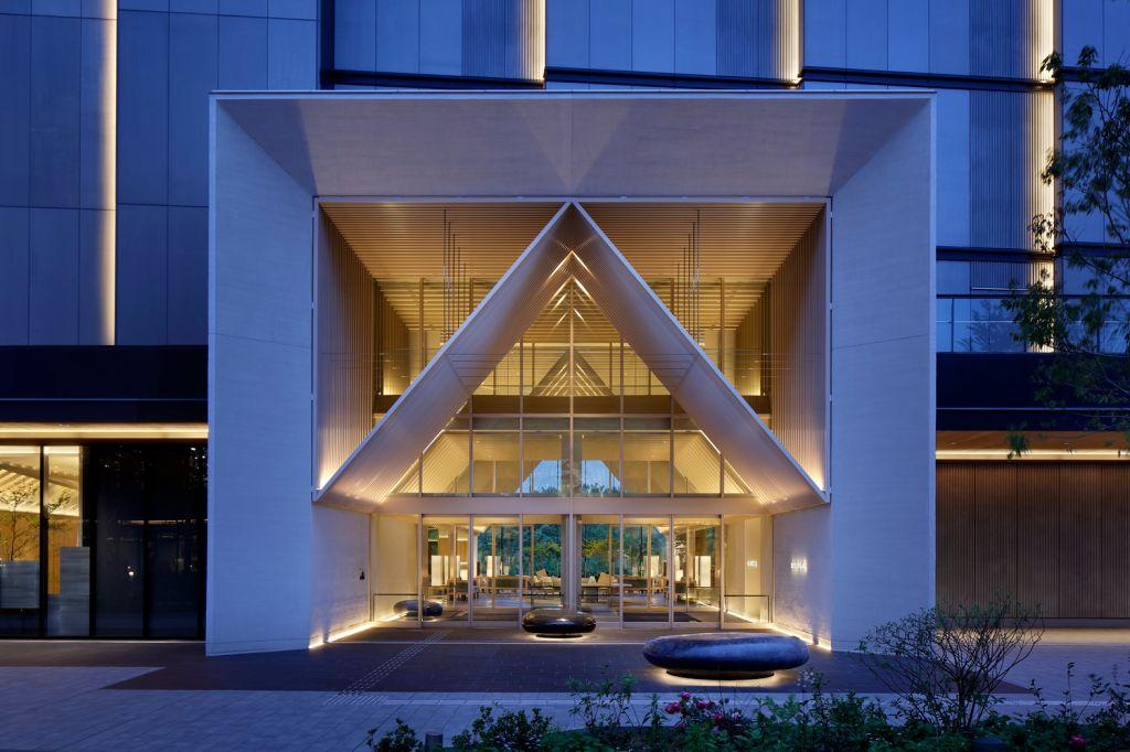 Fachada do hotel iluminada. Composta por um quadrado que abriga a estrutura em formato de cabana