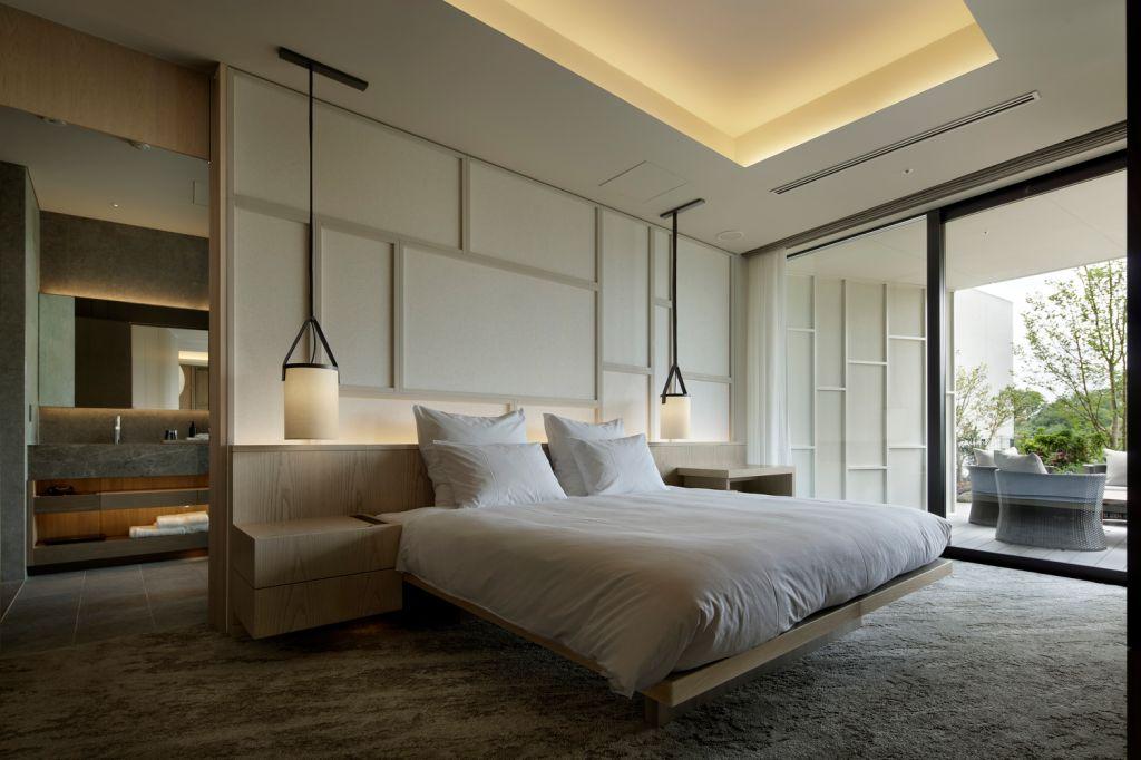 Quarto com cama de casal. Duas luminárias pendentes, uma em cada lado da cama. Parede em madeira branca. Porta deslizante de vidro para a varanda.