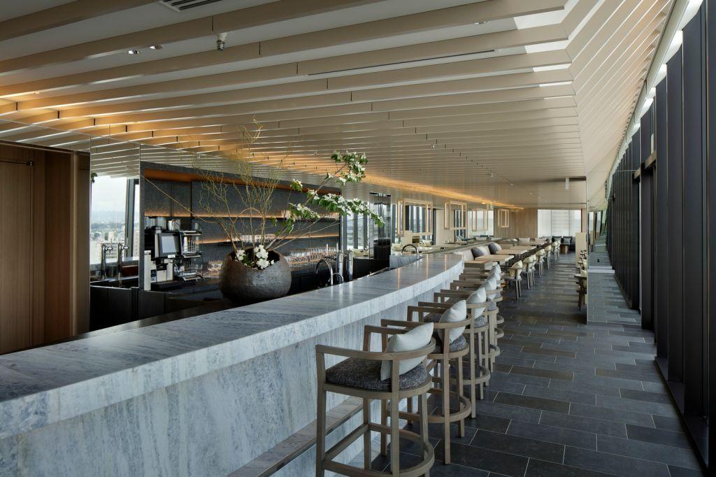 Bar e restaurante. Bancada em granito. Bancos altos enfileirados em madeira. Arranjo floral sobre a bancada. Mesas ao fundo.