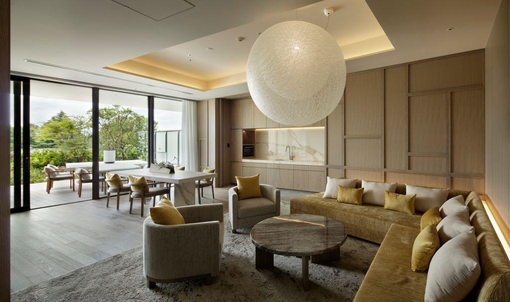 Quarto com sofá de canto amarelo e poltronas. Luminária esférica branca. Paredes e piso em madeira. Janela para varanda com vista para área verde