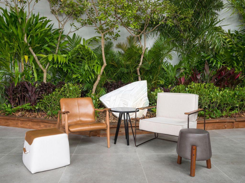 Plantas na parede de uma área externa com poltronas brancas, poltrona de madeira e puff cinza na frente.