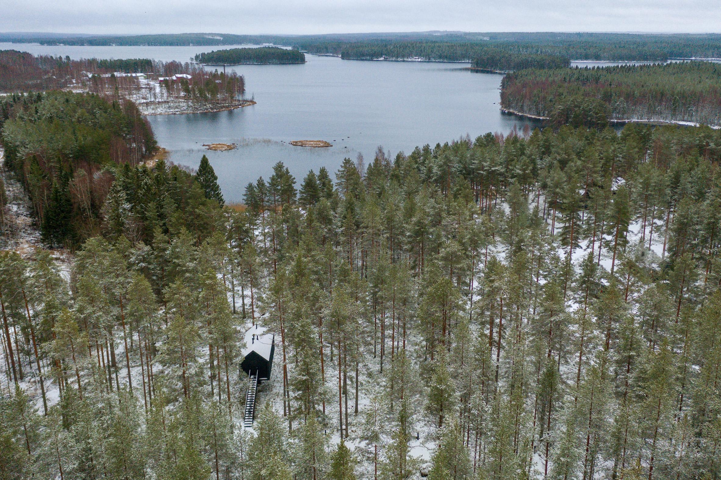 Cabana de cor preta assinada pelo Studio Puisto que elevou-a em uma única coluna. Localizado no Parque Nacional Salamajärvi, na Finlândia.