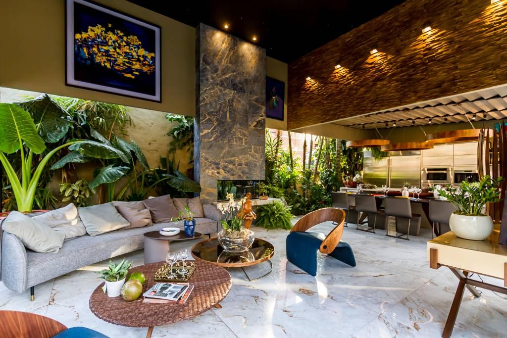 piso de marmore em uma sala de estar com plantas e sofás distribuídos no ambiente