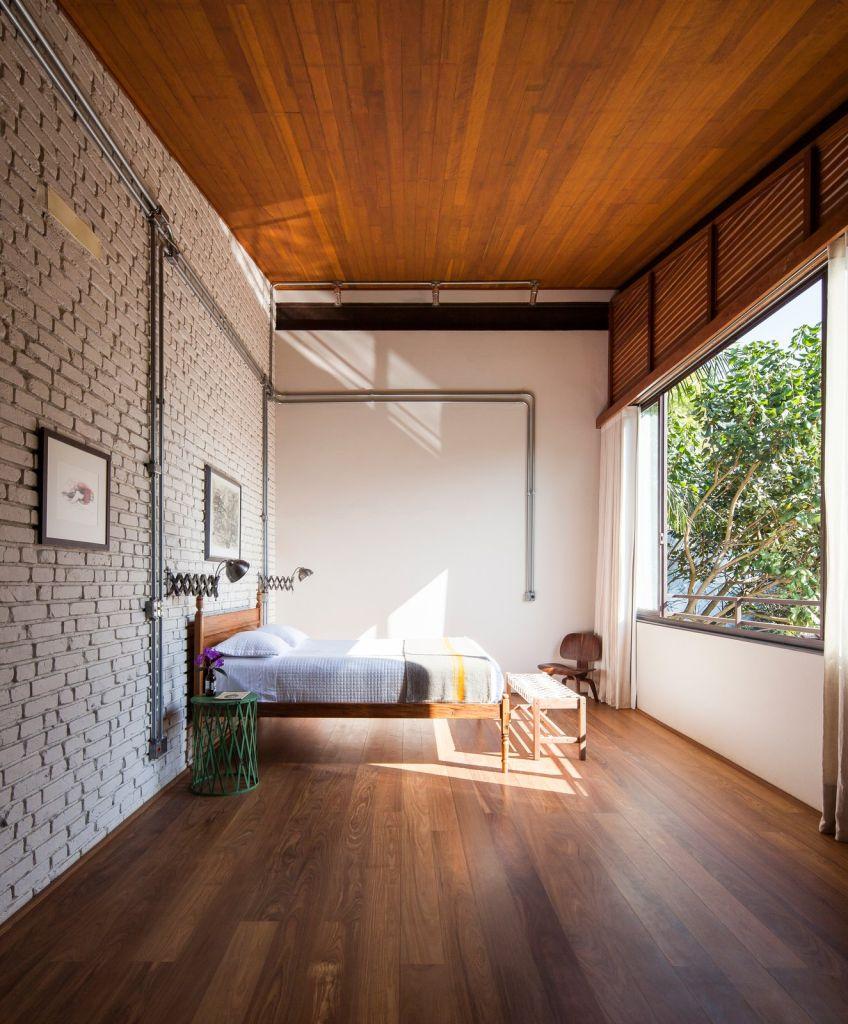 quarto industrial com piso de madeira e janela ampla
