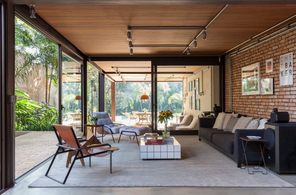 sala de estar com paredes de vidro dando vista para o lado de fora. Uma parede de tijolos foi incluída atrás do sofá