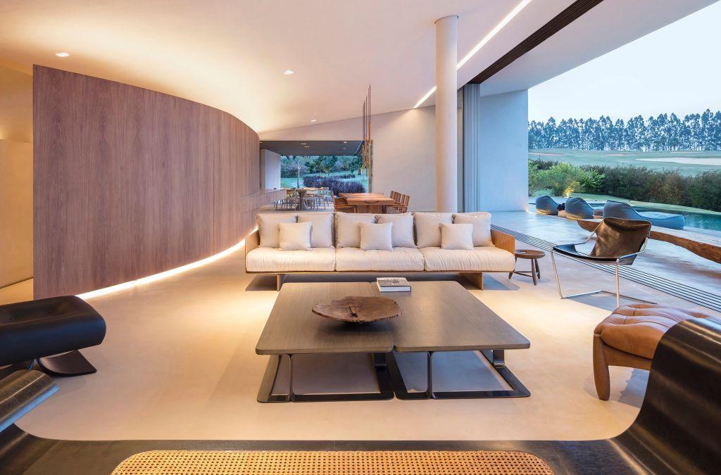 sala de estar com sofá branco, mesa de madeira e móvel de madeira separando o ambiente