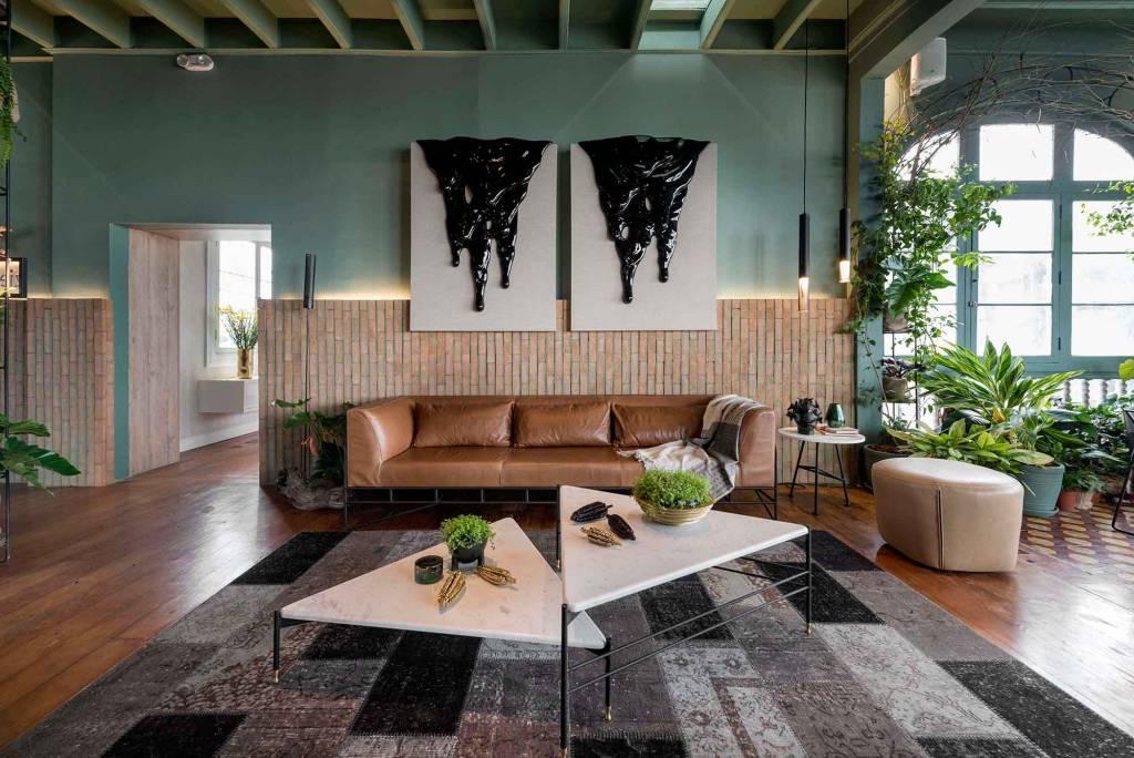 sala de estar com sofá caramelo, mesas no centro brancas em cima de um tapete preto, cinza e branco. Plantas compõe a decoração em suculentas em cima das mesas e samambaias na lateral