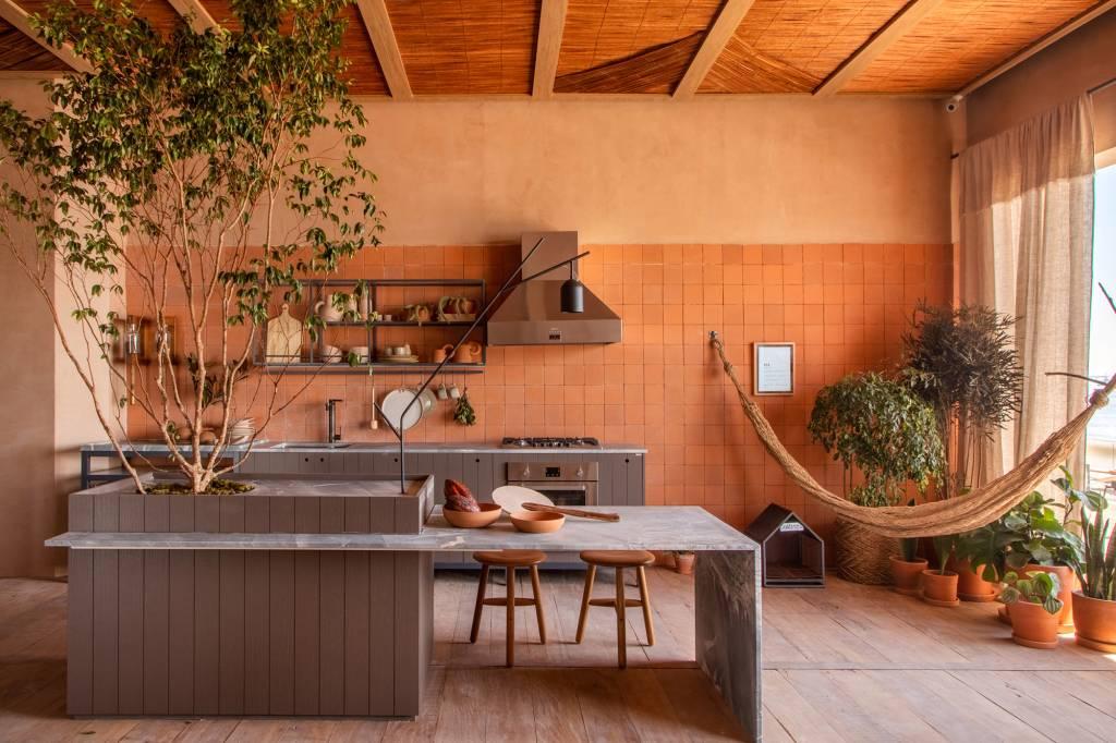 cozinha laranja com ilha no centro em tons de cinza claro com banquetas para recer