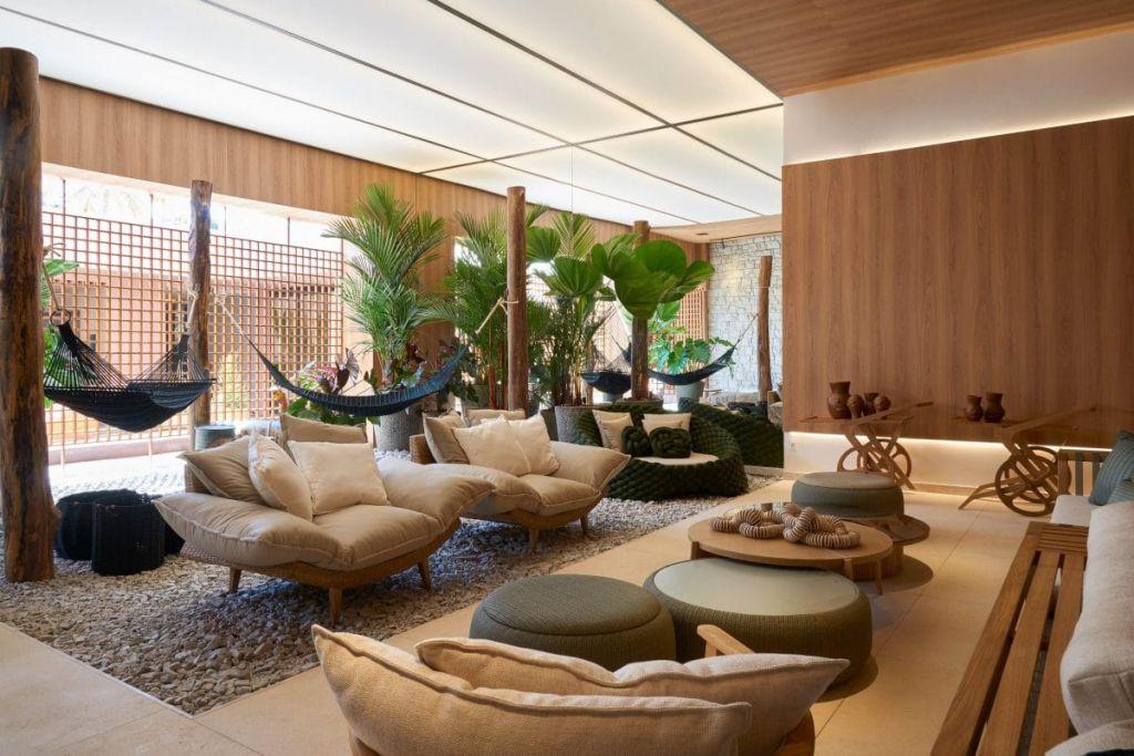 sala de estar com redes espalhadas em tons de azul e madeira clara predominante
