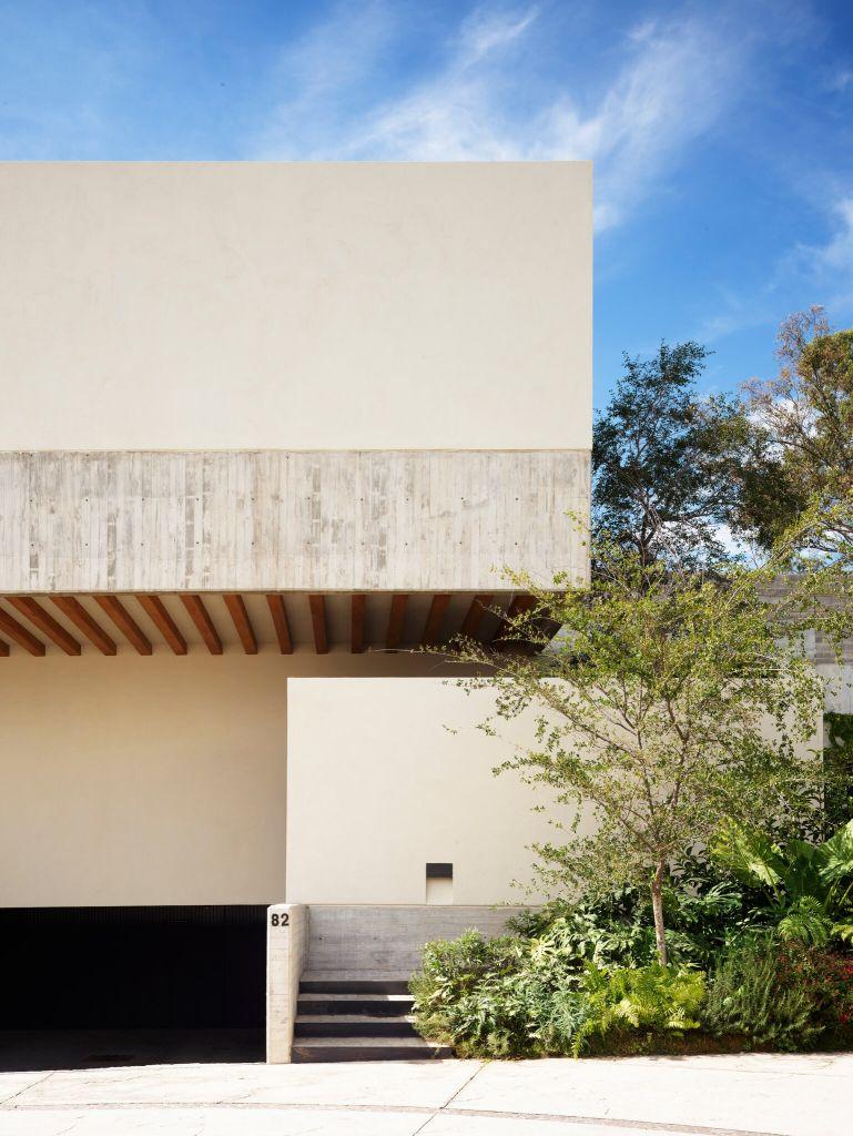 A fachada cega da Casa Entrelomas esconde jardins em formato de terrário, visíveis apenas de dentro