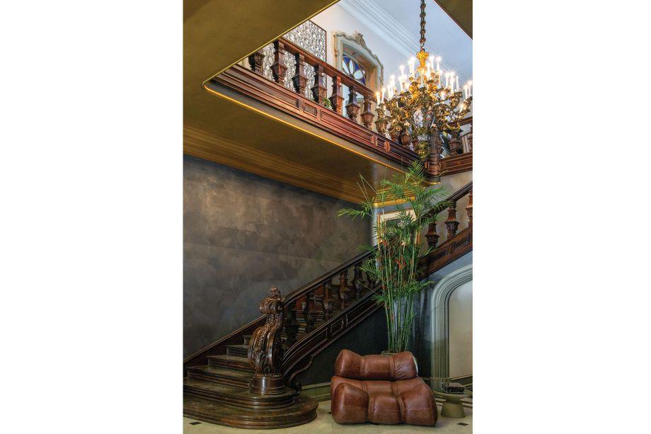 Ao pé da escada esculpida em jacarandá, está posicionado o sofá Fardos, do Atelier Ricardo Fasanello, criando um lounge particular à parte da composição.
