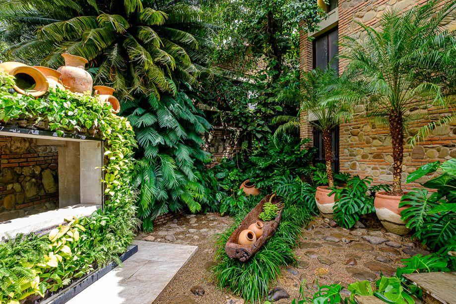 """Jardín de Piedra - Natalia Murillo. Para valorizar a arquitetura original da casa, a paisagista utilizou diversos materiais naturais em seu jardim - como argila, pedra e palha - que também ressaltam a natureza existente. """"No meio da nossa vegetação composta por guaimbês nativos, filodendros e costelas-de-adão, abrimos espaço para uma imponente canoa chiquitana carregada de frutos de nossa terra"""", detalha a profissional. O verde também envolve a bilheteria, enquadrada por jardins verticais."""