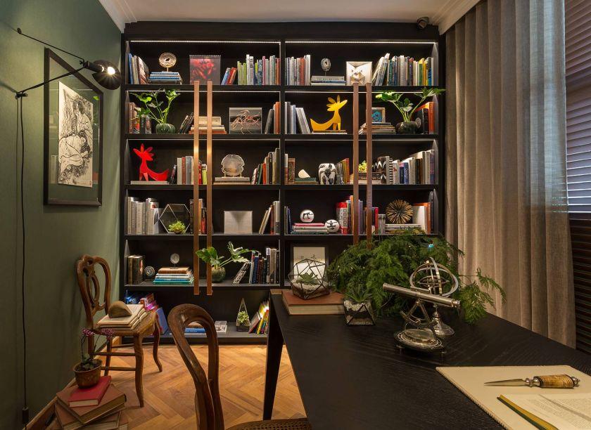 CASACOR São Paulo 2016. Home Office - Patricia Hagobian. O ambiente conta com bastante luz natural, mas não abre mão de um projeto de iluminação com foco nas obras de arte e na mesa de trabalho. A estante repleta convida à leitura.