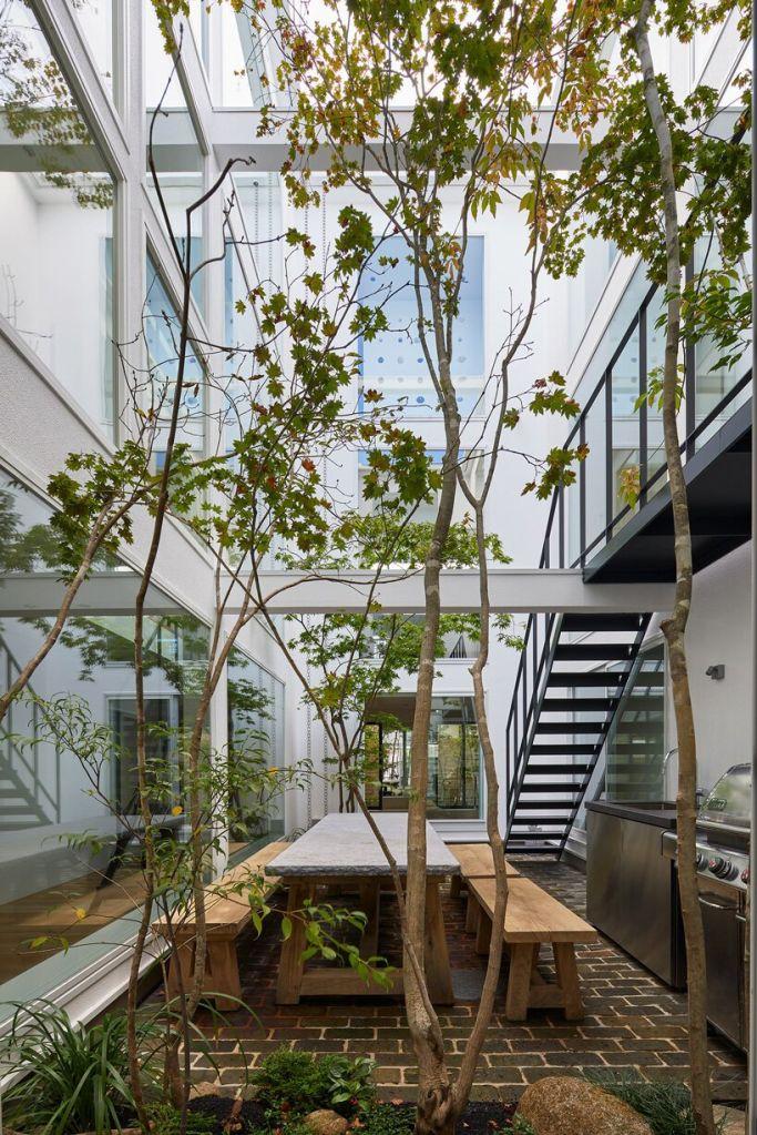 pátio do projeto minimalista com vegetação e árvore no centro. Mesa de convívio para a família e churrasqueira também se encontram no local