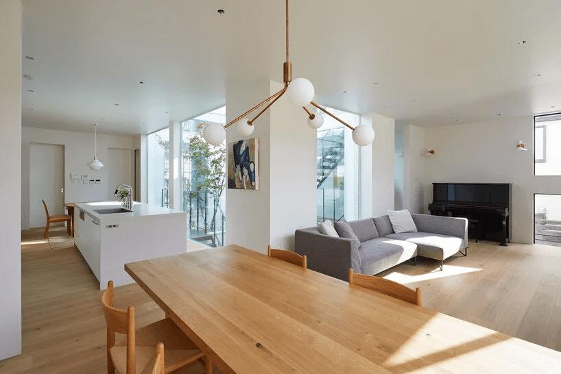 sala de estar integrada a mesa de jantar conta com um lustre moderno no centro