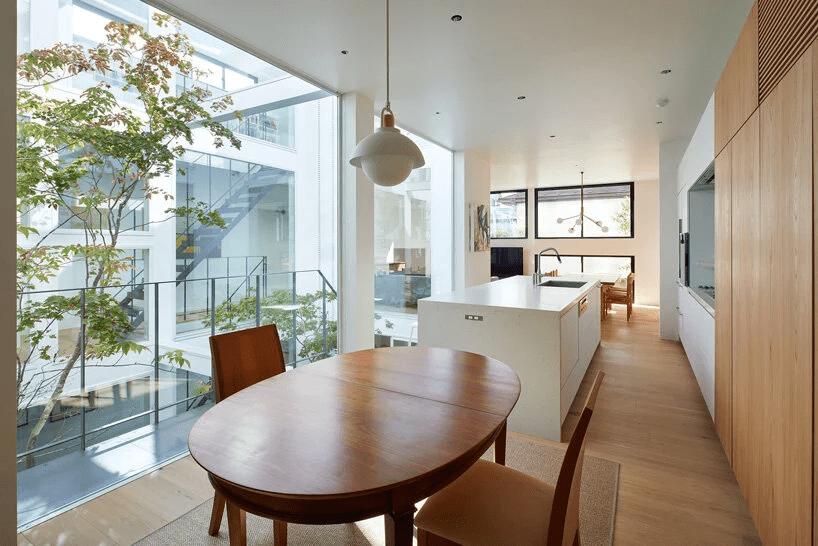 integração da sala de jantar com sala de estar. No centro uma mesa de madeira e ao lado as paredes são cobertas por um armário em marcenaria, deixando o projeto minimalista mais prático