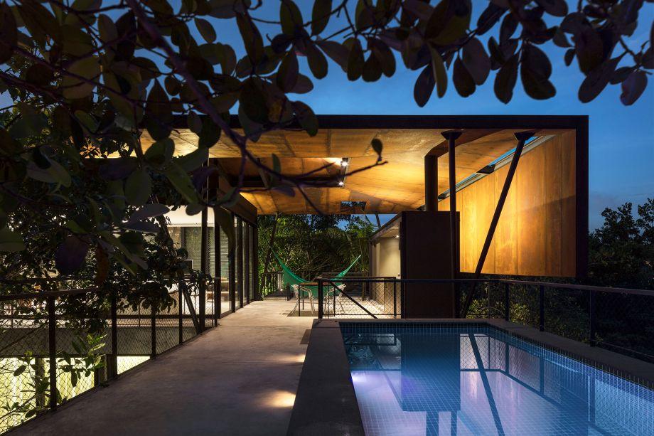 A piscina fica no bloco mais longitudinal, que recebe mais sol. Ao fundo, a platibanda invertida dá privacidade para a cozinha.