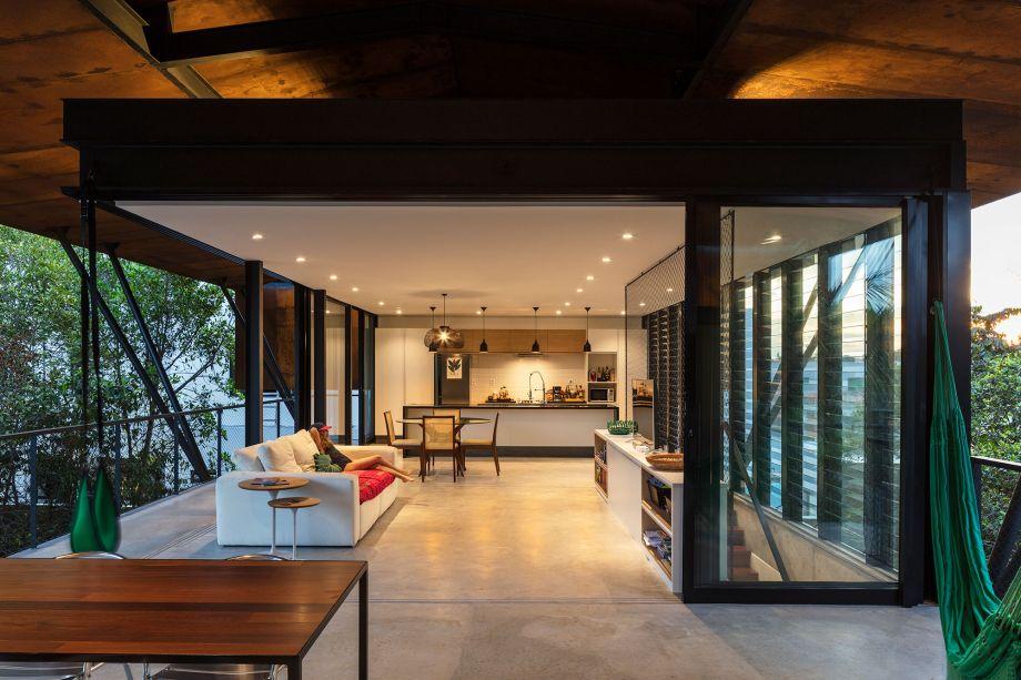 O segundo andar possui panos de vidro que correm sobre trilhos, integrando ou isolando as salas e a cozinha da área externa.