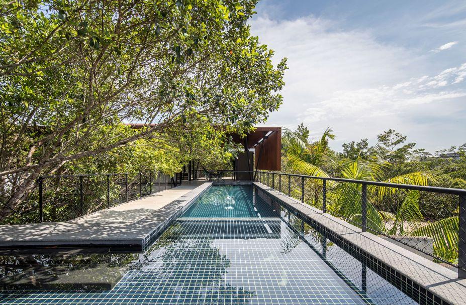 A piscina fica no bloco mais longitudinal, onde a insolação é maior. Ao fundo, a platibanda invertida dá privacidade para a cozinha.