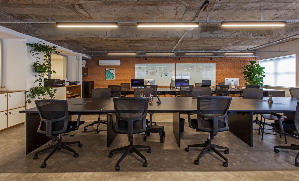Grandes bancadas e cadeiras executivas no escritório da Korman Arquitetos