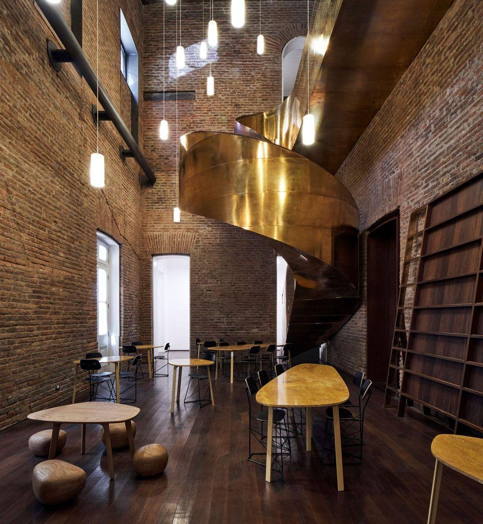 Escada moderna em dourado para servir de ponte entre restaurante e escritórios no Palácio Pereira, nova sede do Ministério da Cultura do Chile
