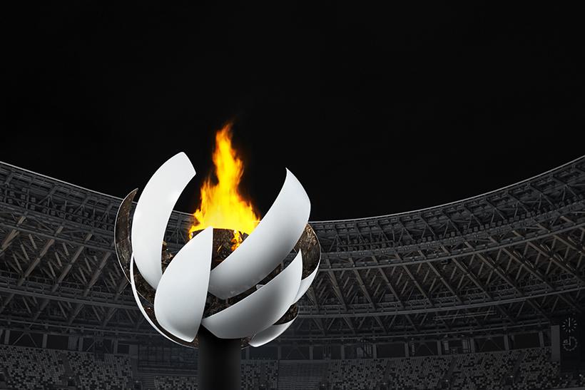 A foto mostra a pira olímpica aberta e acessa dos jogos de Tokyo 2020. O design que remete ao sol é assinado pelo estúdio Nendo.