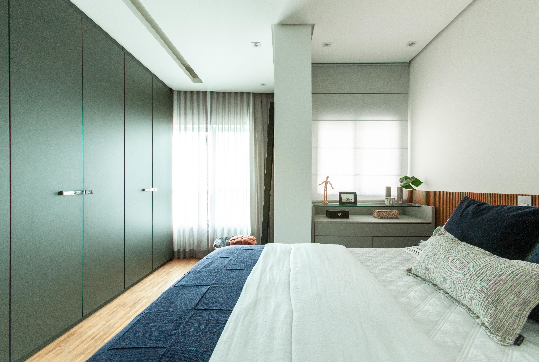Quarto de casal em apartamento contemporâneo conta com painel ripado como cabeceira