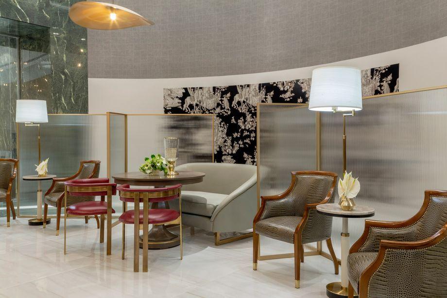 Milena Niemeyer - Lounge Vitrine Flamboyant. Concebido para ser um marco de boas-vindas para os visitantes da mostra e do Shopping Flamboyant, o ambiente é composto por um centro circular de bate-papos, descanso e apoio para conexão. O projeto seguiu a identidade coorporativa do entorno, com tons de vermelho, verde, branco e bege. O mobiliário revestido em couro permite a higienização adequada e as divisórias douradas com vidro canelado garantem a privacidade visual e o distanciamento entre as pessoas.