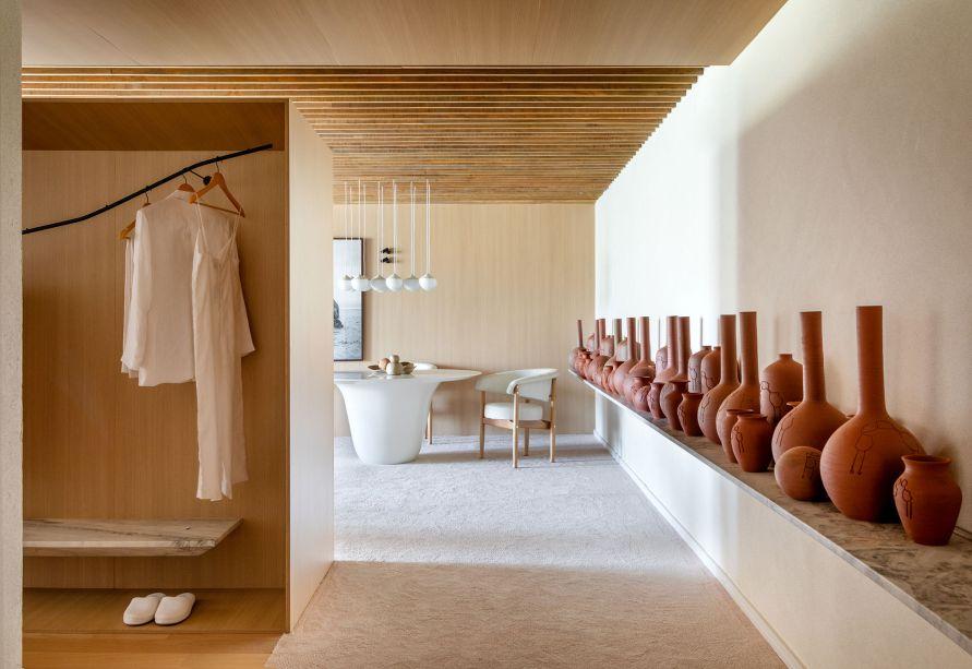 """Quarto Suna Reveev  - Osvaldo Segundo & Arquitetos Associados. """"Suna"""" significa areia em japonês e assim como nome diz, este quarto busca sensações de calma e fluidez. Celebra a beleza imperfeita, a impermanência da vida. A arquitetura  traz diferentes texturas e elementos naturais, unidos por tons claros e linhas sóbrias. O contemporâneo aliado às raízes culturais, o minimalismo combinado ao tradicional, o senso estético puro embasado à função."""