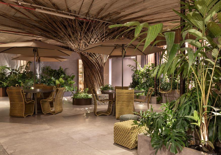 KalilFerre Paisagismo - Meu Verde Particular. Criado pelos paisagistas Elaine Kalil e Maurício Ferre, o espaço de contemplação é um convite para pausa e lazer durante a visita à mostra. Ali, visitantes desfrutam da generosa área verde distribuída em canteiros, vasos e floreiras cimentícias. A vegetação tropical que compõe o paisagismo traz uma variedade de formatos, texturas e cores. No jardim, uma escultura em forma de árvore, feita de bambu, estende os seus galhos até o teto. O toque lúdico vem dos balanços dispostos ao redor da praça.