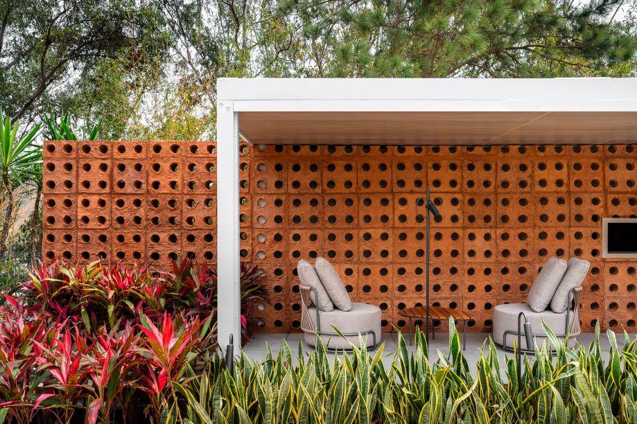 Duo Arquitetos e Droysen Tomich - Café Panini e Jardim Restauro. A arquitetura é mais mediterrânea, com tons neutros e texturas naturais. A unidade da parte interna é dada por um cobogó em adobe, que resgata o tema da mostra, Casa Original. Além de servir para seu uso costumeiro, de ser uma parede vazada, esse cobogó é também utilizado como adega: o recorte de seu diâmetro central é o encaixe perfeito para abrigar uma garrafa, oferecendo a possibilidade de deixá-la em uma temperatura mais baixa.