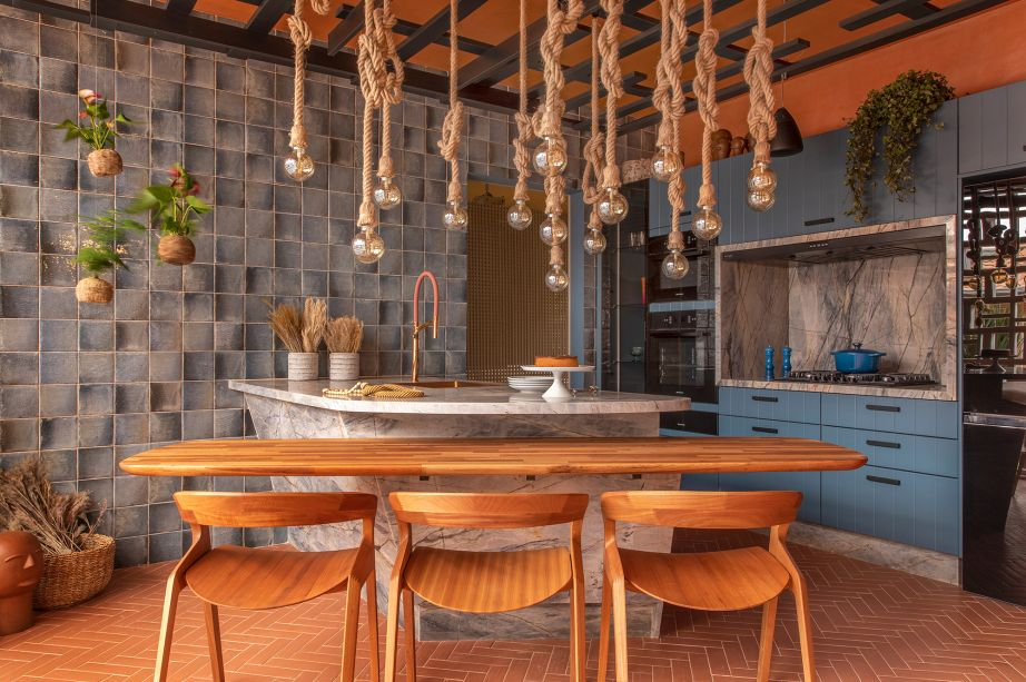 """Adriana Fontana - Cozinha de Ficar. A """"cozinha da casa da avó"""" nasceu para despertar memórias afetivas. E elas aparecem em cada detalhe desse espaço: o piso laranja remete ao terracota das antigas fazendas. E sua clássica paginação em espinha de peixe dá movimento e leva o olhar para o teto de treliça personalizado, ou para a parede de cobogós que oferece luz natural e vista para o """"quintal"""". No balcão central, contrastam o quartzito da bancada e a torneira cor cobre."""