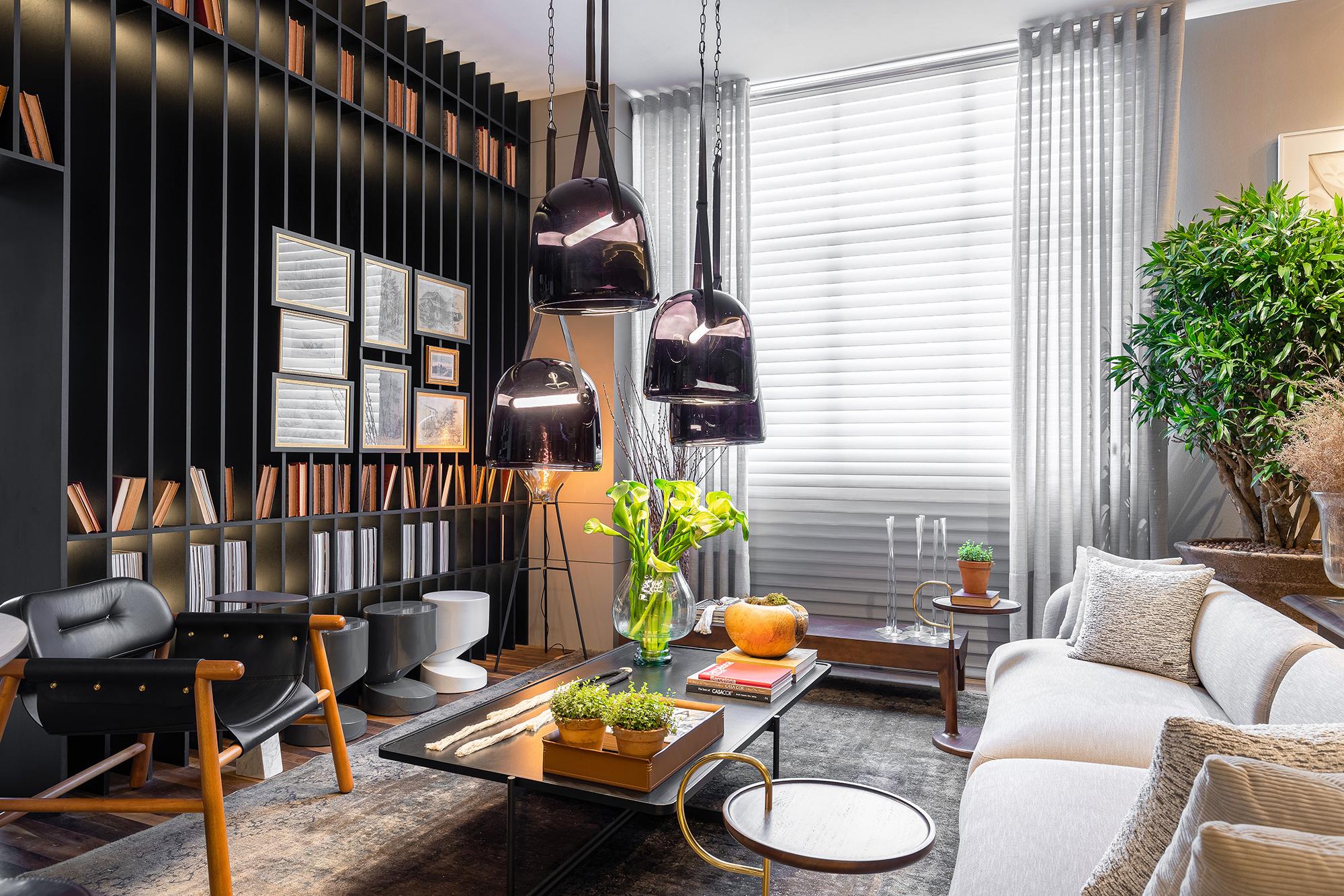 Loft Deca, projeto de Marcelo Lopes para a CASACOR Paraná 2021. Na foto, cozinha com mesa e bancada preta, sofá, tapete e mesas.